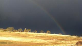 A rainbow in a very dark and grey sky. The field below is lit up in the sunshine.