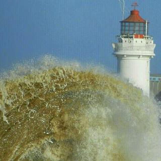 A brown sea wave fills the majority of the picture. Behind is a red and white light house.