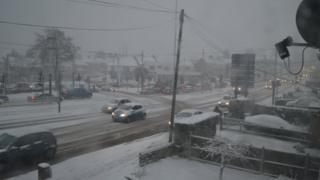 A busy main road with snow on it. The sky is grey and the cars have their lights on.