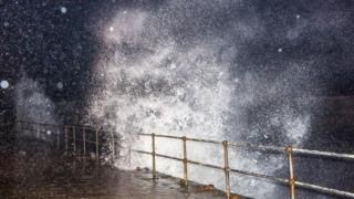 Huge waves coming up over a sea wall and railings. Night time shot.