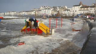 A children's play park by the beach is completely flooded, where the sea has come over the sea wall.