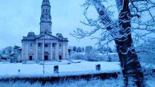 A church and surrounding trees and land are covered in snow.