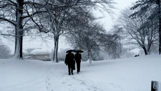 Two people with umbrellas walk through a snow covered park.