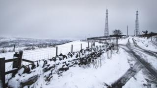 Snow on fields with a view across to other field and hills. A stone wall covered in snow runs through the middle of the picture, leading to two large pylons.