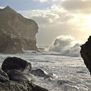A huge wave breaking into a rocky bay. A cloudy and bright blue sky on the horizon behind.