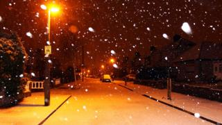 A residential street lit up by streetlamps and the snow that has fallen. Snow falling across the shot, parked cars, pavements and road covered in snow.