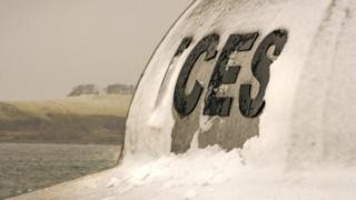 The word ices is written in black capital letters on the side of a metal structure. Snow is covering part of it.