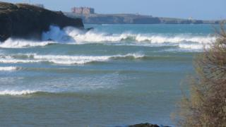 Sea waves hitting headland. Behind are bays in the distance and a large stately home type building on a headland.