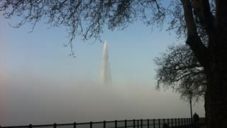 The tall Shard skyscraper appears out of the top of a layer of mist. A tree and walkway frame the picture.