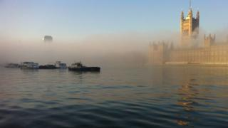 A layer of fog over the river Thames. Boats can be seen and the Houses of Parliament also appearing out of the fog on the right hand side.