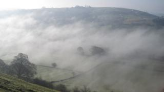 Mist sits in a valley, covering trees and fields.