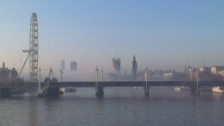 A view of the river Thames with the London Eye wheel and Houses of Parliament. A layer of fog can be seen in the middle of the picture.
