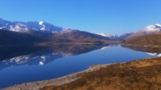 A loch surrounded by snow-capped mountains. Above is clear blue sky.