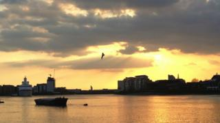 A cloudy sunset, overlooking the River Thames with a boat on it.