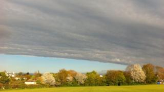A huge grey blanket cloud is taking over the sky. Below is a green cricket field.