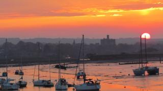 Sailboats in the foreground and a castle in the background. The sun is setting in an orange sky behind.