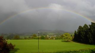A huge rainbow in a grey sky, overlooking green fields and trees.