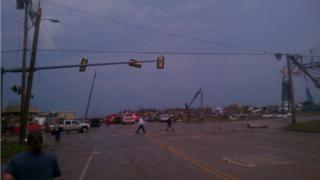 A road intersection with ambulances, people walking in and around the debris. Power lines and posts are broken and fallen.