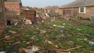 Debris and fencing on grass, houses surrounding.