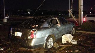 A night time shot of a car with debris on it and the windows smashed in.
