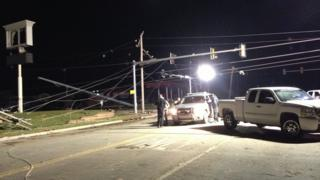 Night-time shot of cars on the road, people outside of their cars talking. Fallen power lines.