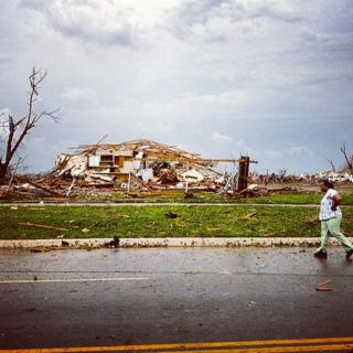 A destroyed house and broken tree. A woman walking on the road is just in the shot.