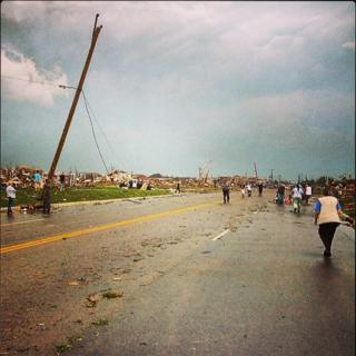 A residential road with houses blown down. Power lines leaning over or snapped off. People walking around.