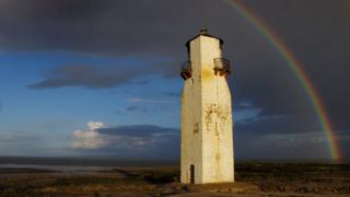 An old white tower on marshland. Grey sky above and a rainbow arching over it on the right.