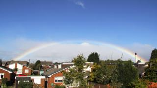 A large rainbow over houses. Cloud and blue sky above.