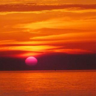 Sun rise over the sea. The whole picture is orange and yellow.