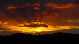 Sun behind clouds, creating yellow and golden brown rays. Silhouetted hills in the foreground.