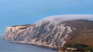 A line of mist creeps over a headland on to a white and black cliff-face. Sea below and to the far bottom right of the picture there are two white houses.