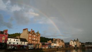 A double rainbow in a grey, cloudy sky. Below are houses and a harbour.