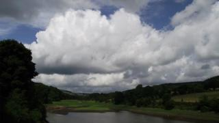 Large white clouds gather over hills and water.