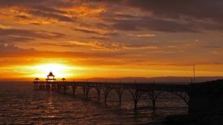 A sun setting over water. There is a silhouetted pier and the sky behind is orange and yellow.