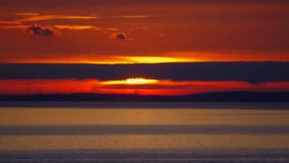 The sun is setting in a bright red and yellow sky. A layer of cloud is across the sun. Water is in the foreground.