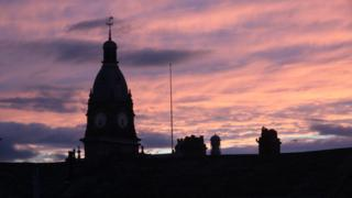 Pink and violet clouds behind a clock tower and chimneys.