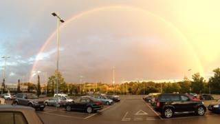 A huge rainbow after a shower. Large clouds behind it and the sun is shining down on trees. A car park is in the foreground.