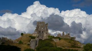 White large clouds behind the ruins of a castle on a hill.