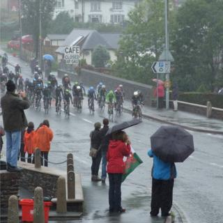 Cyclists on a road and spectators with umbrellas up, as the rain falls down.