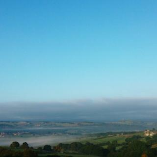 Clear blue sky, a layer of fog below that is sitting over hills and trees.