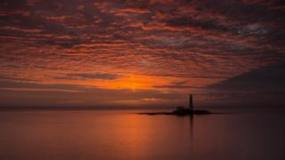 An orange, cloudy sky. Water and a lighthouse below.