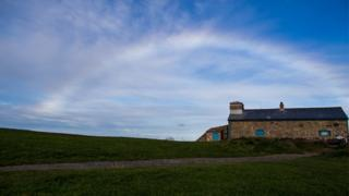 A nearly white rainbow arches over a stone house and grass.