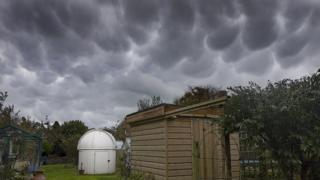 Grey, bulbous clouds. Below is a white astronomical observatory and a shed in a garden.