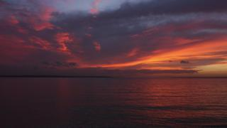 A purple, pink and orange cloudy sky over sea. Land can be seen in the distance.