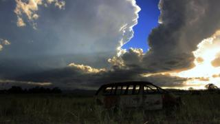 An expanse of cloud has gathered, leaving only a slither of clear blue sky. Fields and the rusted skeleton of a car in the foreground.