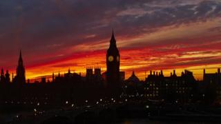 A striking red, orange, purple and yellow cloudy sky over London's Big Ben clock and Houses of Parliament. A bridge is in the foreground.