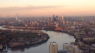 A panoramic view of London and the river Thames. The skyscrapers are glowing in the sunlight and the sky behind is a dusty pink.
