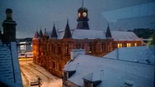 Buildings and roof tops with snow on. The street lamps are on as the sky is a dark grey. A clock tower can be seen on top of a building.