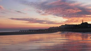 A mother of pearl coloured sky, reflected on a wet beach. Houses and seafront promenade behind.